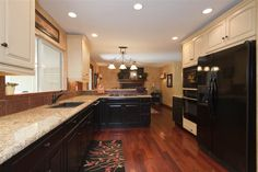 Pretty kitchen with light upper cabinets and light granite with dark lower cabinets.