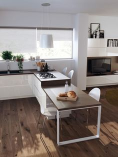 Light and white with wood floor. Small dining area attached to kitchen cabinetry.