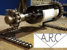 A unique wine bottle holder built from heavy duty roller chain (bicycle chain). It is hand made by an awesome artisan welder in Canada!