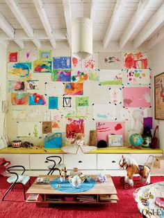 unframed children's art.. this looks like my basement. I love the blue tape to give it pops of color and definition to the space.