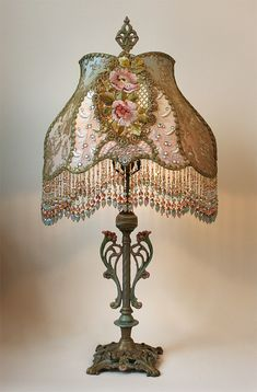 Art Nouveau styled antique table lamp holds a Chateau style shade in soft tones…