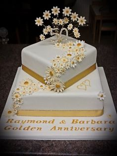 Square cakes possible. Quite liked the gold-centered daisies. Would look good wi… Square cakes possible. Quite liked the gold-centered daisies. Golden Anniversary Cake, 50th Anniversary Cakes, 50th Wedding Anniversary Decorations, Daisy Cakes, 50th Cake, Square Cakes, Wedding Cakes, Silver Weddings, Brooch Bouquets