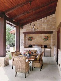 une véranda en pierre à un abri bois, une cuisine exterieure en pierre nichée dans le mur