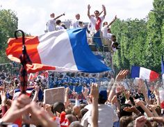Players of the victorious French national soccer wave to supporters during a parade on Champs Elysees avenue in Paris, where hundreds of thousands of wildly happy people poured 13 July for the victory parade by World Cup winners France aboard an open-topped bus. Waving the French flag, jumping, shouting and singing in joy, the crowd awaited the arrival of the French side, at least 30 minutes behind schedule because of the numbers out on the streets.