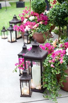 Top 9 Backyard Party Ideas - Create a lushly lit oasis on your ordinary patio with a few potted plants and lanterns. This look is perfect for intimate gatherings with friends or families, sharing wine in the soft, summery evenings. Recreate this look by filling stone and cement pots with fresh flower plants and topiaries, and clustering them along the edge of your patio. Next, place a few metal lanterns of different sizes in front of the potted flowers, bring soft light to your display.