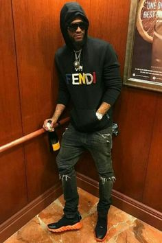 2055dec310e Dave East is wearing a logo hoodie and Runway sneakers