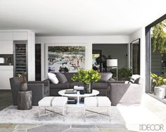 Courtney Cox's Malibu home - Minotti cocktail table, sofa and armchairs designed by Haenisch, the floor lamp is by Christian Liaigre, and the stools are by Paul McCobb; a Massimo Vitali photograph and the rug is by the Rug Company.