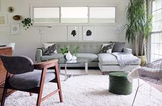 TV room furniture: light grey/taupe sectional with warm wood mixed in and potted plants.