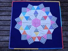 """Eye catching Michael Miller Fabrics Mirror Ball Dots make this fun EPP a bright and shiny """"Fairground Attraction"""" made by Pennie from Tuppence Ha'penny Quilts.  """"I decided it needed a plain rich coloured backing, and navy blue won over purple. I quilted it by stitching in the ditch with #Aurifil 50wt in white...""""  To see more visit http://tuppencehapennyquilts.blogspot.com/2013/09/fairground-attraction-and-giveaway.html"""