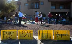 """People gathered to mourn and pay tribute at the spontaneous grassroots memorial which grew up outside Congresswoman Gabrielle Giffords' office following the shooting of Giffords and 18 others at her """"Congress on Your Corner"""" event on January 8, 2011 in Tucson, Arizona. Giffords was gravely wounded and 6 other people perished in the shooting. Photo by Gina Ferazi"""