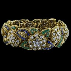 Elegant sculptural bracelet designed as a strap of diamond-set flowerhead motifs inbetween sapphire and emerald-set leaves each outlined with a gold twisted wire Van Cleef & Arpels, Paris 1955