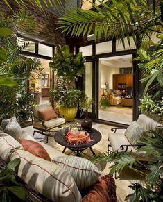 Jardim interno. Ares de lazer interna com sofás e muitas plantas só redor.