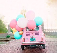 Pink pastel vintage Volkswagen Beetle with gold, pink, and teal balloons attached to car.