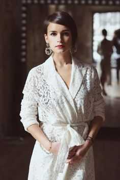 Miroslava Duma is wearing a lace bathrobe trench with ginormo earrings and it's amazing.