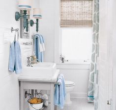 This bathroom's classic color palette is accented with traditional-style hardware in sparkling chrome. A DIY project ties the look together—inexpensive blue craft ribbon trims the edges of wall sconces to match the towels and shower curtain. Get the look with products from our boutique at Wayfair.com