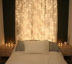 white lights behind a sheer curtain behind the bed