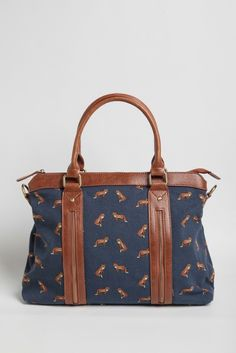 Whimsical and darling, this navy canvas satchel is adorned with an enchanting fox print and accented with brown faux leather trim and handles. Perfected with burnished gold-toned hardware and zip...