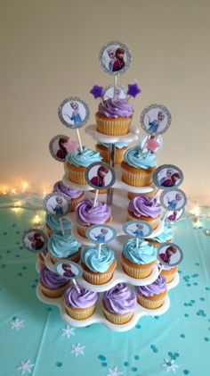 FROZEN cupcakes.  Tiffany Blue and Lavender iced vanilla cupcakes with shimmering sugar crystals on top with Anna and Elsa cupcake toppers ordered off of Etsy.