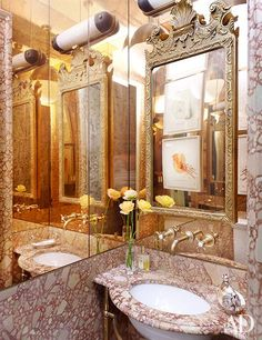 Mirror and marble line a powder room. Cool how the wallpaper matches the marble sink.