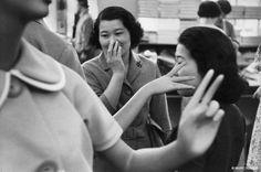 Tokio, 1958. En una tienda, las mujeres japonesas, según su tradición, ocultan la sonrisa con la mano y el muñeco parece imitarlas.