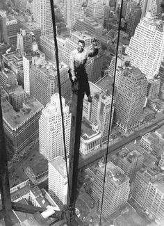 1930's construction worker in NYC. Photo b/w, city view, high up, waving, smiling, male, man, not afraid of hights ? history.