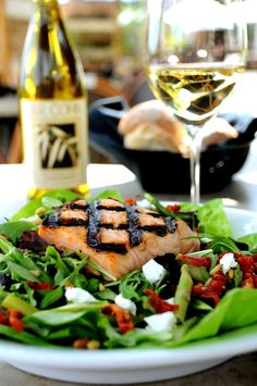 Woodfire grilled salmon on a bed of field greens tossed with goat cheese, pine nuts, sun-dried tomatoes, asparagus & white balsamic dressing. (Brimstone Woodfire Grill)