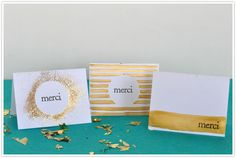Make your own cards! •heavy white cardstock •spray adhesive •gold glitter •metallic gold paint •'merci' stamp •black ink pad •2 inch hole punch •scissors •fine tip paint brush •wide paint brush