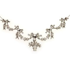 A Belle Epoque diamond necklace, of garland style, centred with a giardinetto motif, articulated beneath a ribbon bow surmount, to graduated swags tied by ribbon bows suspending foliate drops, millegrain set throughout in platinum with old brilliant and rose-cut diamonds to an 18 carat white gold trace link backchain, circa 1910.