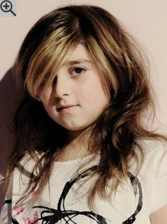Long hairstyle with highlights for young girls. A deep side part lets the bangs to fall over one eye.