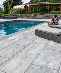 This stunning pool deck feels like a relaxing retreat in the comfort of this homeowner's backyard. Cool grey tones are a striking contrast to the deep blue of the pool. Decks Around Pools, Above Ground Pool Landscaping, Swimming Pool Landscaping, Pool Pavers, Pool Decking Concrete, Pool Tiles, Simple Pool, Rectangle Pool, Pool Landscape Design