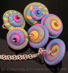 Polymer clay spirals by ketztx4me www.flickr.com/people/8989180@N02/  Made into spinner pendants by redcrow