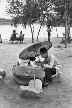 Henri Cartier-Bresson CHINA. Beijing. An older professor corrects his class papers by the lake in the newly built King Chan Park. 1958.