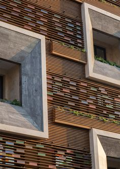 Faceted window frames project from the slatted timber and stained-glass facade of this apartment block in Tehran designed by Keivani Architects