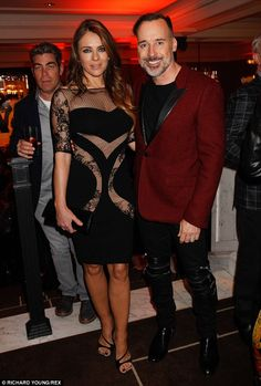 Strike a pose: The Bedazzled beauty's daring dress matched her pal David's bondage-style trousers perfectly
