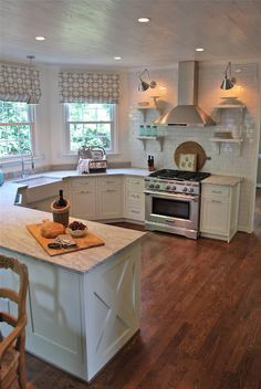Love this kitchen - white cabinets, u-shape, apron sink, windows by sink! Change floors to white wide planks; window ledge for plants to sit; covered cabinets by stove.