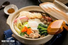 Savory nabeyaki udon topped with chicken, carrots, shrimp tempura, kamaboko, and mushrooms in an umami dashi soup,