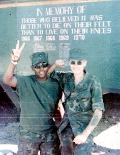 """Two recon Marines of the 1st Marine Division, Camp Reasoner, 1970. The sign behind them reads, """"In Memory of those who believed it was better to die on their feet than to live on their knees."""""""
