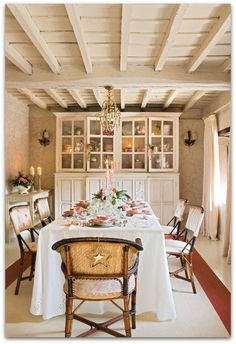 Love rustic ceiling, faint print on walls, white table cloth covering entire table, wood look of chairs