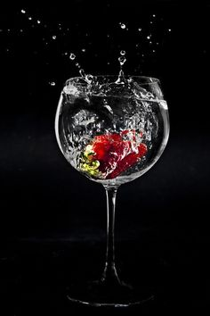 Photo of a strawberry falling in to a glass of water, making a splash. taken with a fast shutter speed, using Canon speedlites.