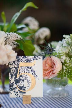 A navy floral print table number with gold typography, a striped tablecloth and blush and white peony centerpieces for a spring wedding table. Reception Decorations, Wedding Centerpieces, Centrepieces, Table Decorations, Wedding Stationary, Wedding Invitations, Invites, Our Wedding, Dream Wedding