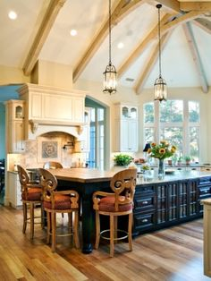 Such a charming kitchen. Seems so whimsical to me, with those chairs, the arched beams, the lights. <3