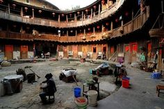 Chinese basket weaver sitting in the courtyard of a round house, Chinese: Tulou, adobe round house of the Hakka minority, Tianluokeng Building Group, Hukeng, Fujian, China, Asia : Stock Photo