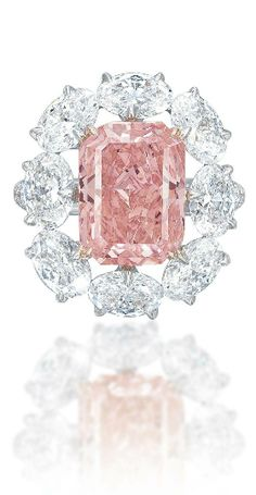 A MAGNIFICENT COLOURED DIAMOND RING Set with a fancy vivid pink rectangular-cut diamond, weighing approximately 5.18 carats, within an oval-shaped diamond surround, mounted in gold...