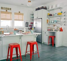 A stand mixer tucks in the corner by the refrigerator and shelves above house mixing bowls and baking necessities.