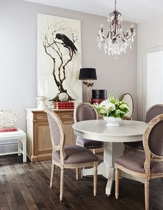 Light grey walls in an ecclectic dining room with light unvarnished timber floors, light purple dining chairs and modern white pedestal table designed by interior designer Samantha Pynn