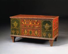 "A PAINT-DECORATED BLANKET CHEST Possibly Georgia, dated 1871 The rectangular hinged lid with molded edges opening to a compartmented interior fitted with a sliding panel above a conforming case decorated with stylized foliate motifs in green and yellow on red and green grounds centering the initials ""JH"" over ""1871"" above a conforming molded base, on tapering feet with yellow detailing on a red ground 21in. high, 37in. wide, 16in. deep"