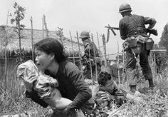 Under sniper fire, a Vietnamese woman carries a child to safety as Marines storm the village of My Son, near Da Nang, searching for Viet Cong insurgents, April 25, 1965. As was typical in such situations, the men of the village had mostly disappeared, and the remaining villagers revealed little when questioned by the Marines