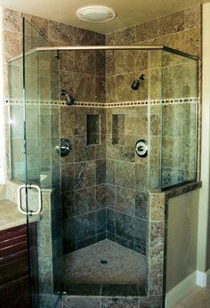 Corner tile shower. Has dual shower heads and shampoo cubbies.