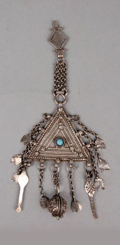 Oman | Headdress ornament; silver and blue plastic bead | ca. 1950s | Probably used to pin a veil to a headdress although it is also found as a necklace pendant. The design is called 'Baluchi style' and is favoured by the Baluch people of Oman who form a large and totally integrated section of the population. || For similar examples see: Avelyn Forster, 'Disappearing Treasures of Oman' (Clevedon, 2000); and Jay Gluck and Sumi Hiramoto Gluck, 'A Survey of Persian Handicraft' (Tehran, 1977).