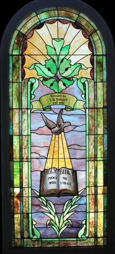Vintage Stained Glass Window DESCRIPTION: Vintage Romanesque stained glass window with dove and Bible. Featuring 2 Timothy 4:2. In original wood frame. We can replace glass that has text on it.
